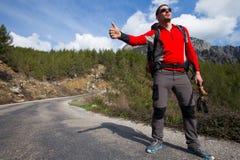 Haciendo autostop al viajero intente parar el coche en el camino de la montaña Imágenes de archivo libres de regalías