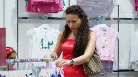 Haciendo compras en la tienda, haciendo compras departamento de la ropa del ` s de los niños la mujer joven, madre elige las cosa almacen de metraje de vídeo