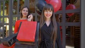 Haciendo compras, mujer joven sonriente que muestra muchas de bolsas de papel con las compras en fondo de la novia bonita con los metrajes