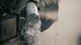 Haciendo de piezas de metal en la máquina del torno en la fábrica, virutas del metal, concepto industrial, vista delantera metrajes