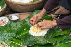 Haciendo el embalaje de Chung Cake, de la comida lunar vietnamita de Tet del Año Nuevo al aire libre con las manos y los ingredie Fotos de archivo libres de regalías