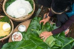 Haciendo el embalaje de Chung Cake, de la comida lunar vietnamita de Tet del Año Nuevo al aire libre con las manos y los ingredie Foto de archivo