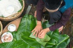 Haciendo el embalaje de Chung Cake, de la comida lunar vietnamita de Tet del Año Nuevo al aire libre con las manos y los ingredie Imagenes de archivo