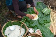 Haciendo el embalaje de Chung Cake, de la comida lunar vietnamita de Tet del Año Nuevo al aire libre con las manos y los ingredie Imagen de archivo