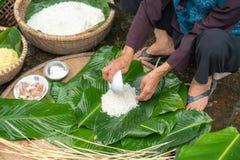 Haciendo el embalaje de Chung Cake, de la comida lunar vietnamita de Tet del Año Nuevo al aire libre con las manos y los ingredie Imagen de archivo libre de regalías