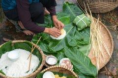 Haciendo el embalaje de Chung Cake, de la comida lunar vietnamita de Tet del Año Nuevo al aire libre con las manos y los ingredie Fotografía de archivo libre de regalías
