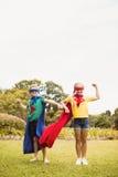 Haciendo frente a la opinión los niños que llevan al super héroe vista la presentación para la cámara Imagen de archivo