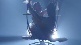 Haciendo girar en el aire a dos gimnastas Fondo negro del humo Silueta Cámara lenta Cierre para arriba metrajes