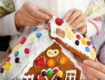Haciendo la casa de pan de jengibre de la Navidad junto Imagenes de archivo