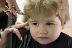 Haciendo la experiencia del corte de pelo agradable Corte de pelo dado del pequeño niño Pequeño niño en salón de la peluquería Ni fotografía de archivo libre de regalías