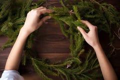 Haciendo la Navidad enrruelle con las manos en fondo de madera Foto de archivo