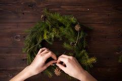 Haciendo la Navidad enrruelle con las manos en fondo de madera Foto de archivo libre de regalías