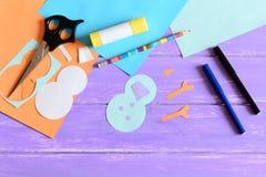 Haciendo a niños tarjeta de papel del invierno step Las piezas del muñeco de nieve cortaron del papel, tijeras, marcadores, lápiz Fotos de archivo