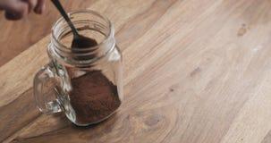 Haciendo que el cacao bebe en el tarro de cristal con la manija en la tabla de madera, añadiendo el polvo de cacao Imagen de archivo libre de regalías