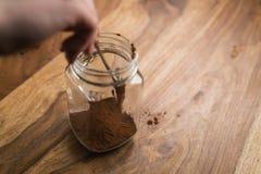 Haciendo que el cacao bebe en el tarro de cristal con la manija en la tabla de madera, añadiendo el polvo de cacao Foto de archivo libre de regalías