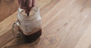 Haciendo que el cacao bebe en el tarro de cristal con la manija en la tabla de madera, revolviendo el cacao Imagen de archivo