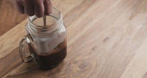 Haciendo que el cacao bebe en el tarro de cristal con la manija en la tabla de madera, revolviendo el cacao Foto de archivo libre de regalías