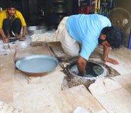 Haciendo Rotis (pan) en el tandoor (horno) Foto de archivo libre de regalías