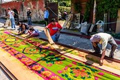 Haciendo serrín teñido la alfombra santa de jueves, Antigua, Guatemala Imagen de archivo