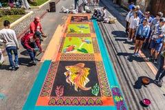 Haciendo serrín teñido la alfombra santa de jueves, Antigua, Guatemala Foto de archivo
