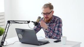 Haciendo un podcast, fluyendo y concepto de difusión de radio Hombre joven en el ordenador con un micrófono en el estudio o en almacen de video