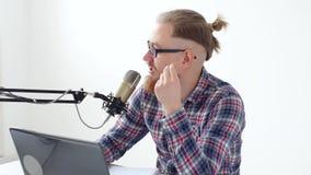 Haciendo un podcast, fluyendo y concepto de difusión de radio Hombre joven en el ordenador con un micrófono en el estudio o en metrajes