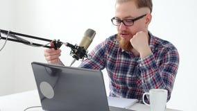 Haciendo un podcast, fluyendo y concepto de difusión de radio Hombre joven en el ordenador con un micrófono en el estudio o en almacen de metraje de vídeo