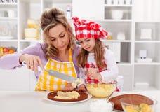 Haciendo una torta - mujer y niña Fotografía de archivo libre de regalías