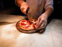 Haciendo y cociendo una pizza de salchichones fresca fuera de un horno caliente imagen de archivo