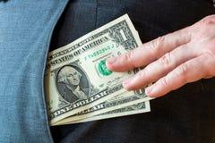 Hackafack - stjäla dollarräkningar ut ur ett fack arkivbild