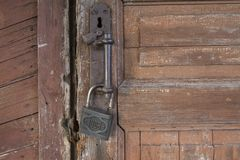 Hacked ancient padlock on the old door stock image