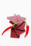Hacken der dunklen Schokolade mit frischen glühenden Paprikapfeffern Lizenzfreie Stockbilder