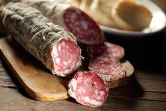 Hackendes Brett mit geschnittener Salami stockbild