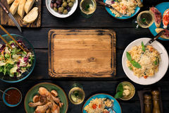 Hackendes Brett, Risotto, briet Hühnerbeine, Snäcke und Weiß Stockbilder