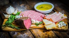 Hackendes Brett von Assorted kurierte Fleisch, Käse und Honig mit ro Stockfotografie