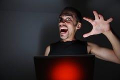 Hacker. Computer hacker with laptop in dark room Stock Images