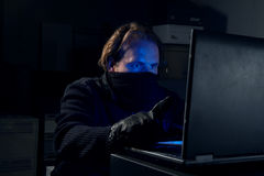 Hacker. Man in black in front of a laptop Stock Images
