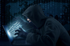 Hacker activity stealing user information. Portrait of male hacker wearing black mask and stealing user identity Stock Photo
