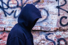 Hacker against a brick wall. Royalty Free Stock Photography