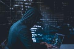 Hacker anônimo com o portátil na frente da segurança do cyber do código binário fotografia de stock royalty free