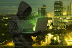Hacker with anonymous mask with laptop while standing. Against white background royalty free stock images