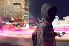 Hacker anonymous using smartphone on the street. At night Stock Images