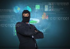 Hacker with arms crossed in front of blue background with digital graphics Royalty Free Stock Photography