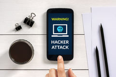 Hacker attack concept on smart phone screen with office objects Royalty Free Stock Photo