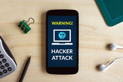 Hacker attack concept on smart phone screen on wooden desk Stock Images