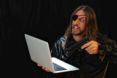 Hacker attack. Pirate attacks computer with a gun royalty free stock image
