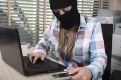 Hacker attacks from phone and computer. Woman in the office situation royalty free stock photography