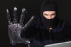 Hacker in balaclava with fingers spread out Royalty Free Stock Photo