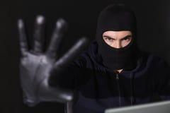 Hacker in balaclava gesturing and looking at camera Stock Photo