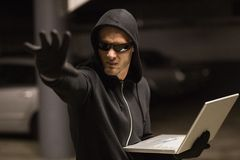 Hacker in balaclava gesturing and using laptop Stock Photography